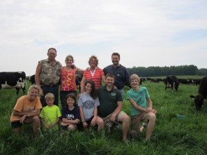 Members from the fifth and sixth generation of Klessigs pose for a photo in the pasture in front of their cows.