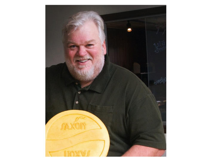 Jerry Heimerl holding a wheel of Saxon Creamery cheese