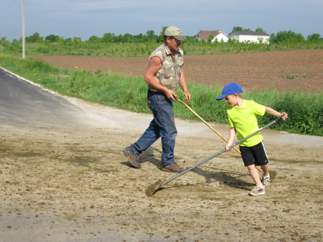 Father and son clean the road after the herd crossed it heading to pasture.