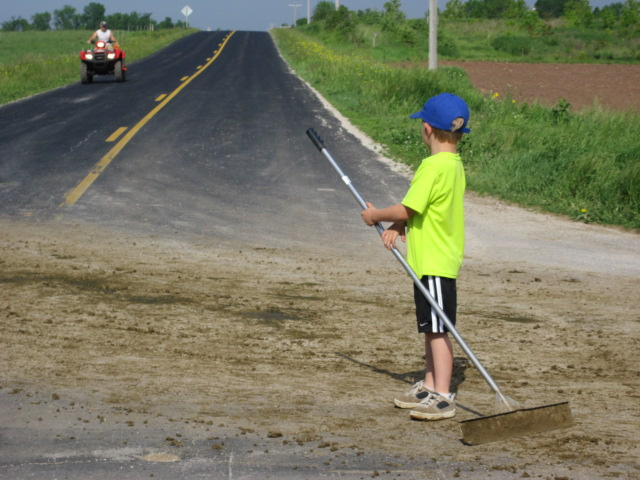 Peter Klessig helps clean the part of the road where the herd crossed.
