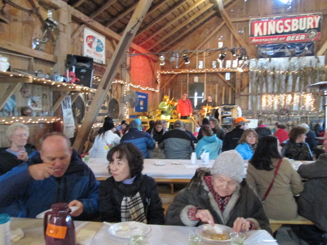 Margret Klessig, the farm matriarch, enjoys her pancakes alongside Fred and Young Sun Klessig.